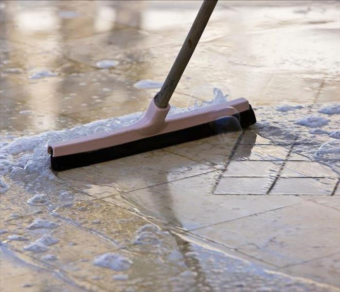 Standing water pushed off of a floor with a squeegee.