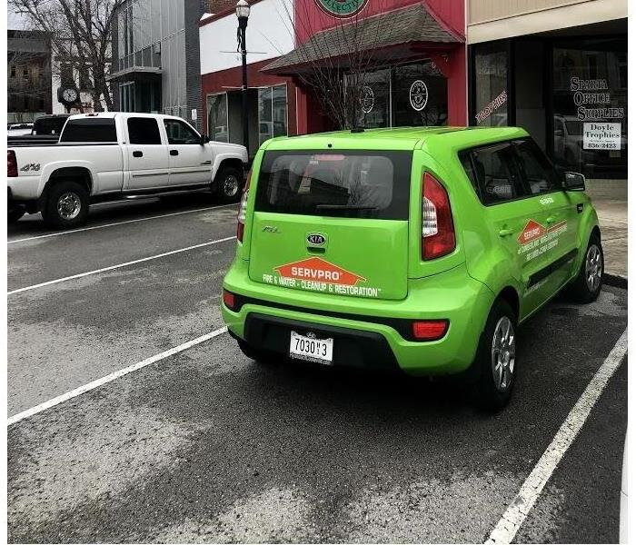 A SERVPRO vehicle parked in front of a business.